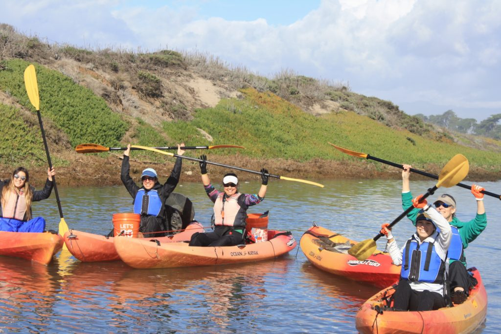 Five women smiling and holding up paddles while kayaking on the Elkhorn Slough.