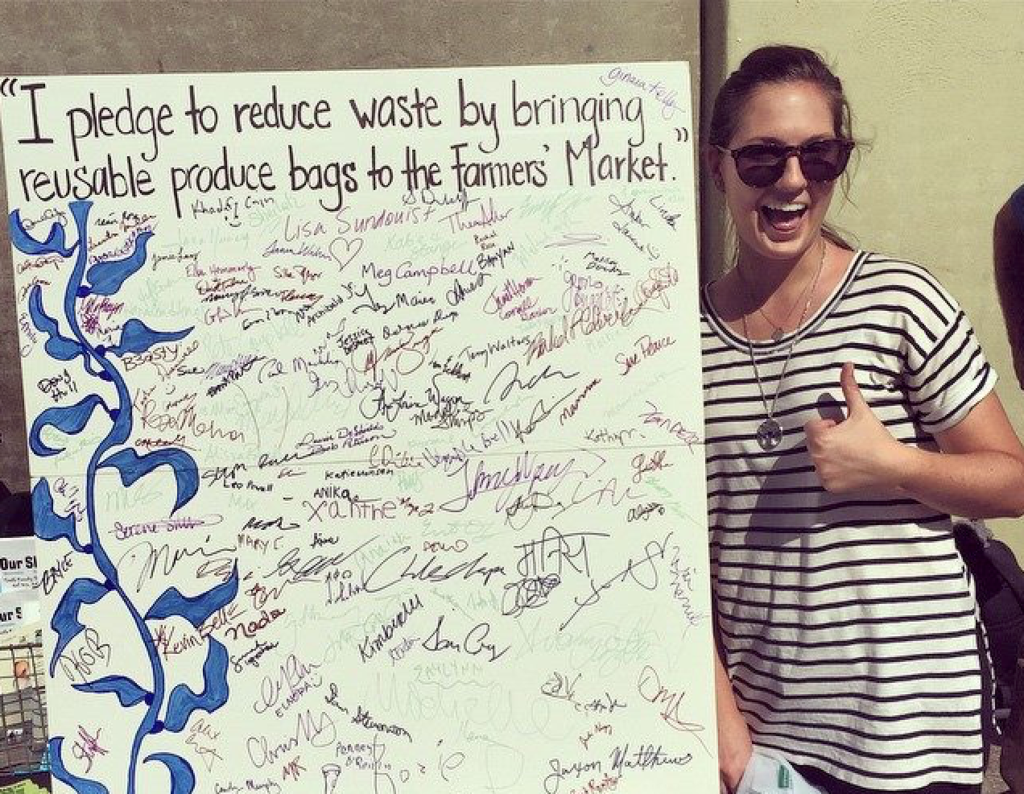 Woman standing beside chart paper with pledge to reduce waste.