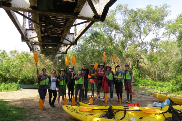 A dozen people stand under a bridge by a river with paddles in their hands and yellow kayaks lay in front of them.