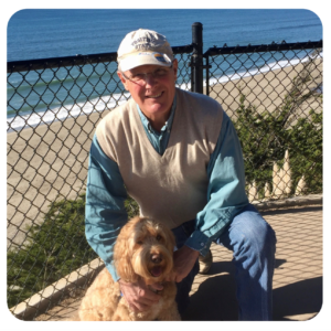 A man crouches down to smile beside his curly small dog with a fence in the background and sand and the ocean in the distance.