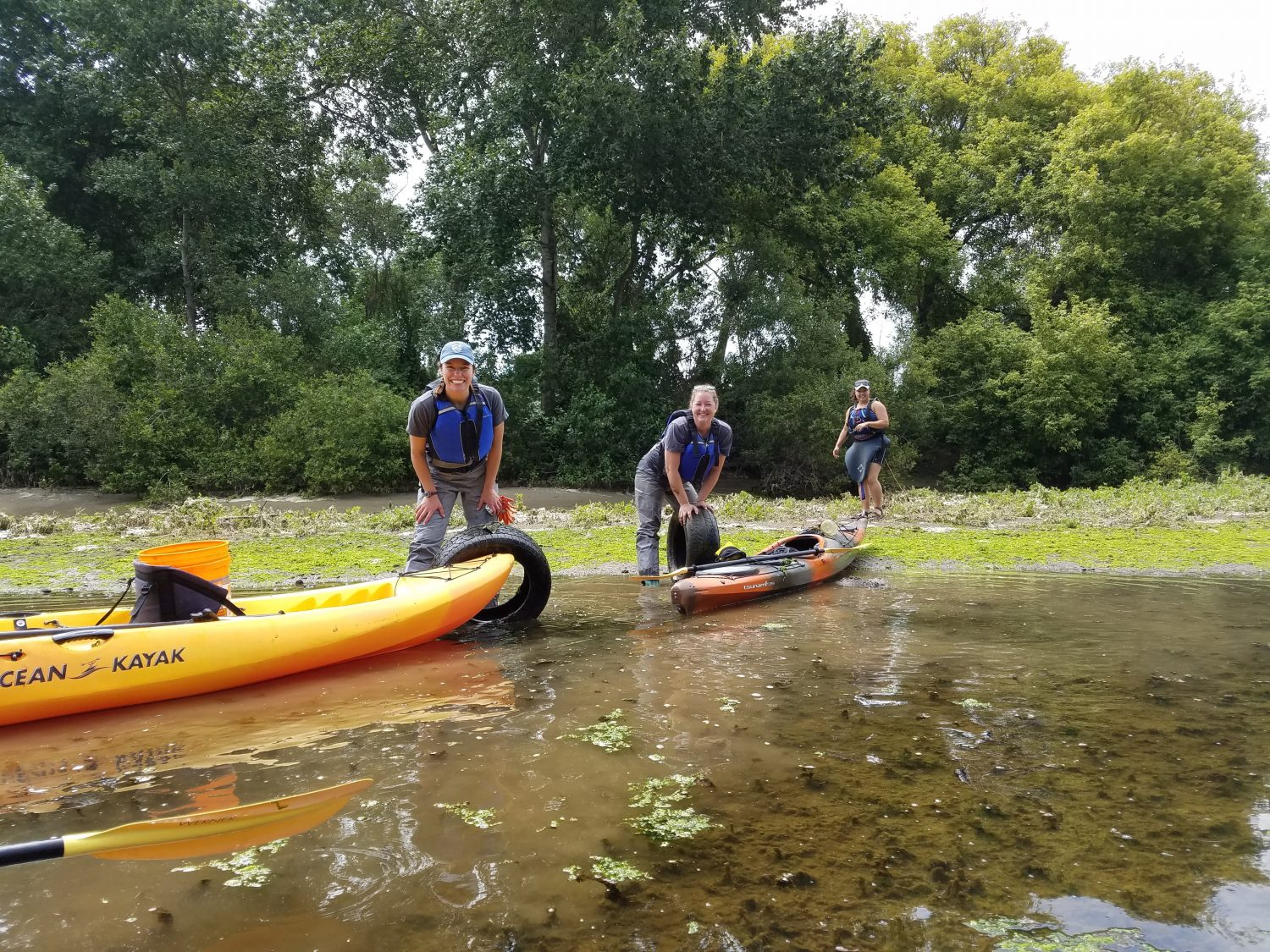 3 women standing on a riverbank beside kayaks and taking part in a Save Our Shores cleanup.