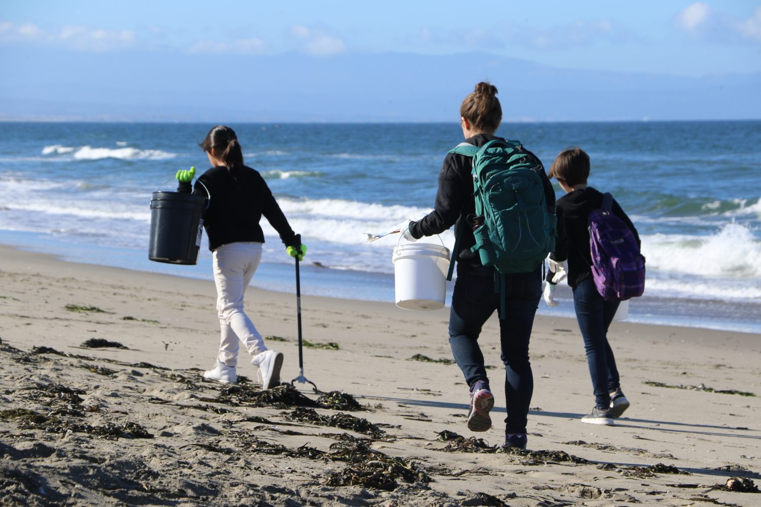 Three girls walk on a beach on a clear blue day with buckets and gloves in hand.