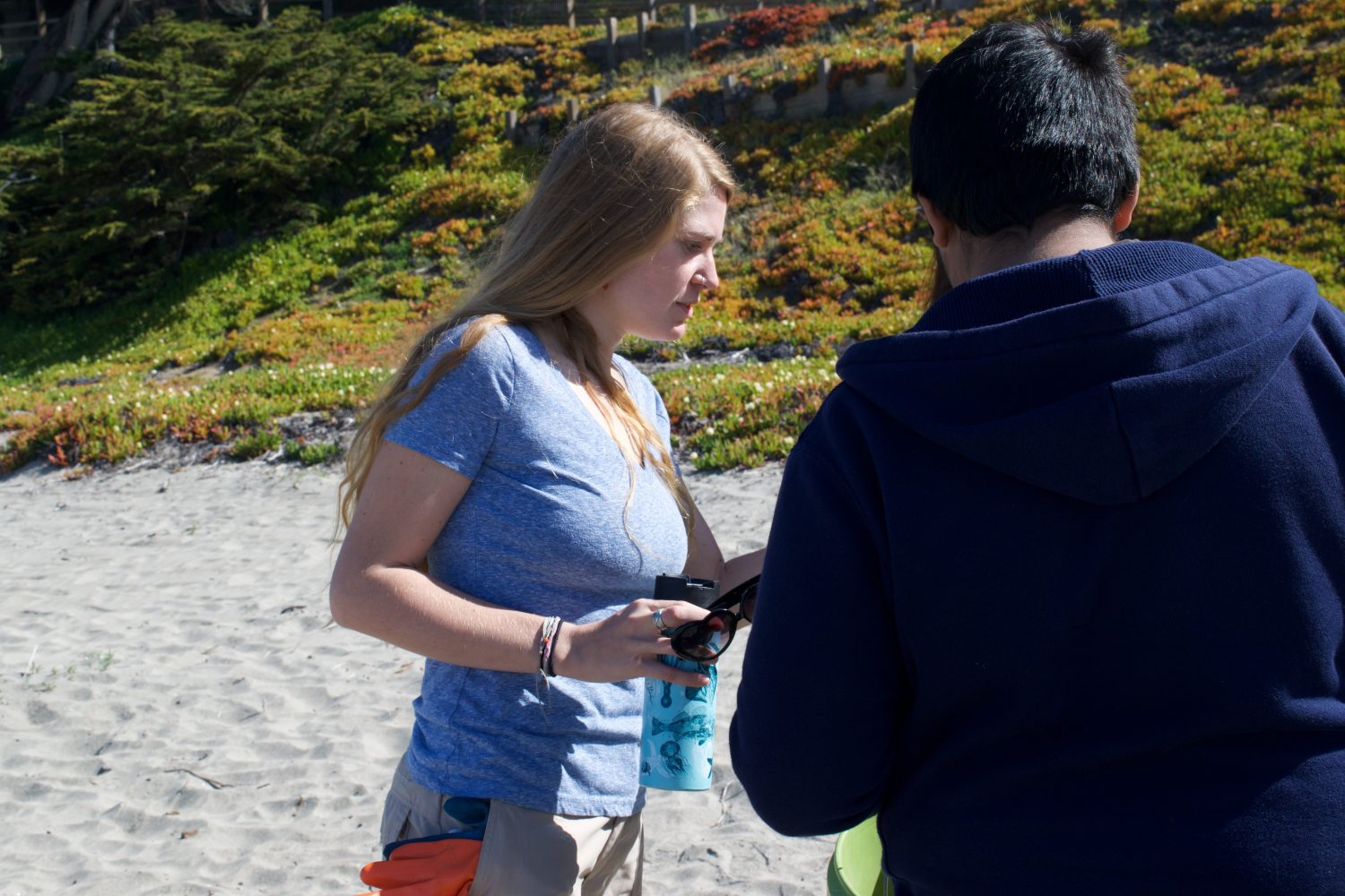 A young blond woman looks at a document in a young boys hands. There is sand and a big hill covered in ice plant behind them.
