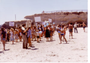 Dozens of people in the early 1980's gather for a protect on a beach with signs and blue balloons and a bluff in the background.