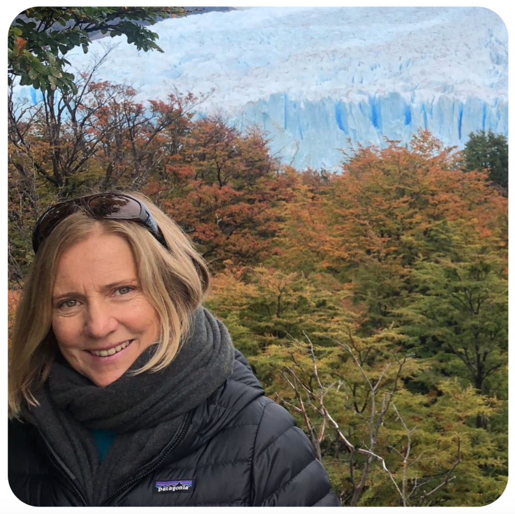 A smiling blond woman in a black down coat stands before green and orange trees with glaciers in the far distance.