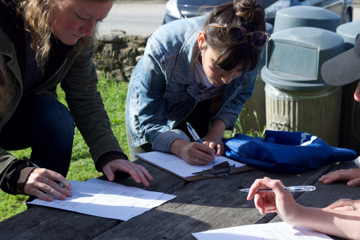Three women sign waivers on a picnic table near green grass and trash cans.