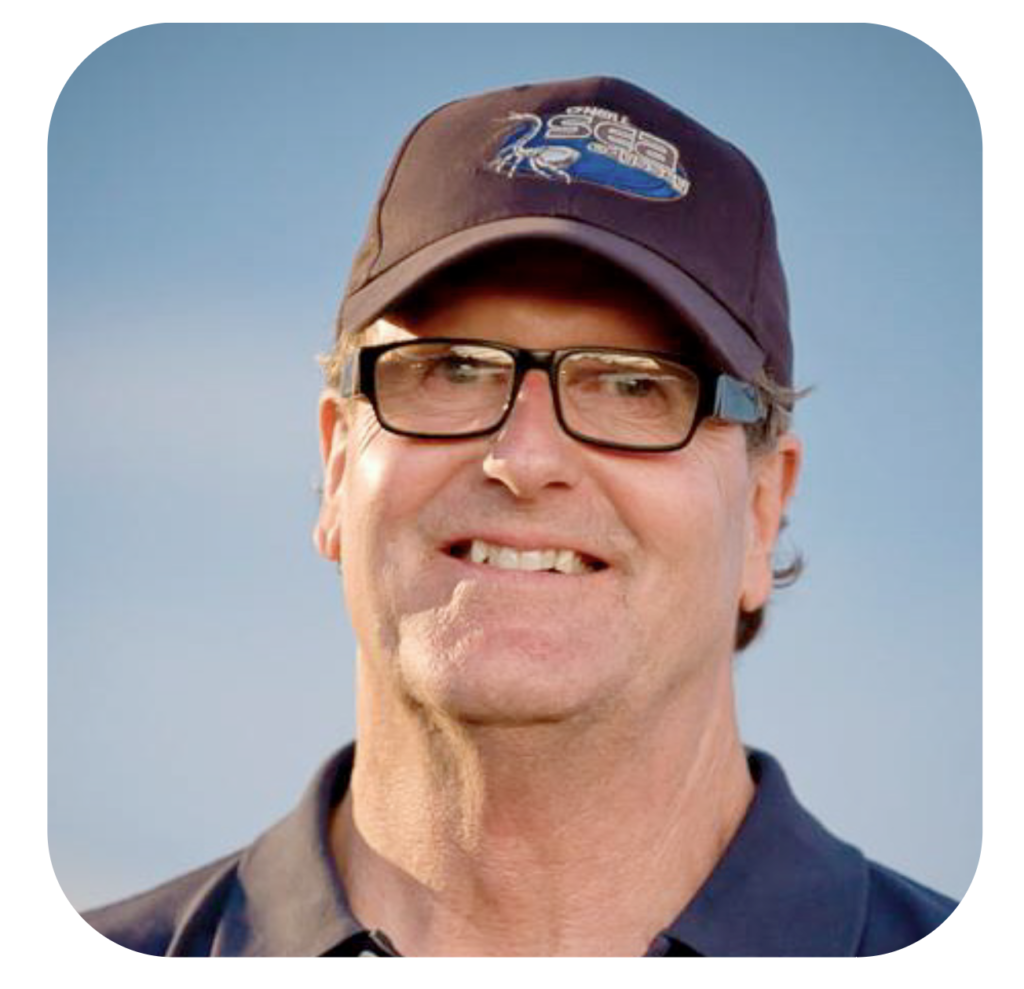 Close up image of Dan Haifley who is wearing a navy O'Neill Sea Odyssey hat, black glasses, and a blue collared shirt with a blue sky in the background.