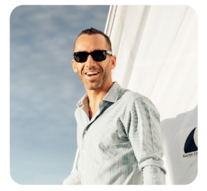 Tyler Fox is smiling in front of a sail boat sail and blue cloudy skies. He has short brown hair, sunglasses, and a blue and white striped shirt on.