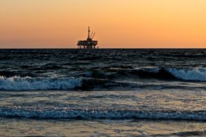 A lone offshore oil rig sits out in the blue ocean waters with a peach sky in the background.